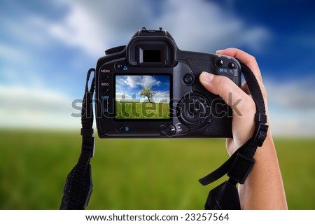 woman taking a landscape photography with a digital photo camera - OOF background to enphasize the viewfinder image in focus - stock photo