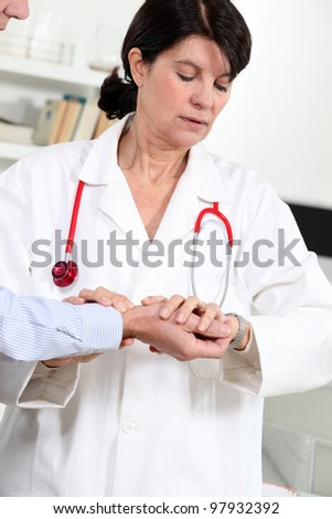 Woman taking a patient's blood pressure - stock photo