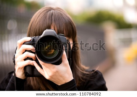 Woman taking a photo in the city during the day with bokeh background - stock photo