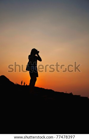 Woman taking a photography silhouette in sunset background