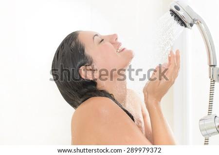Woman taking a shower enjoying water splashing on her  - stock photo