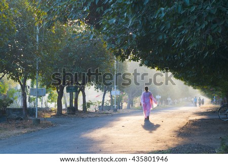 Woman taking a walk at park in the golden light during autumn morning.