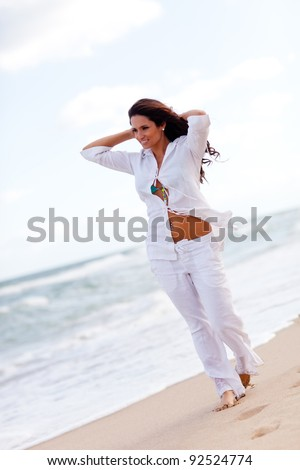 Woman taking a walk at the beach and relaxing - stock photo