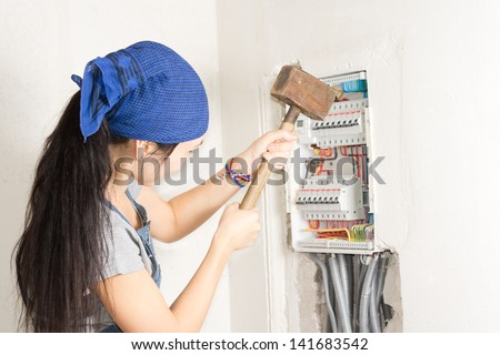 Woman taking aim at an electrical fuse box with a large wooden mallet in an effort to solve her supply problems - stock photo