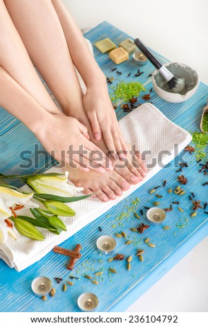 Woman taking care of her legs on the bath towel in spa with flower, candles and herbs on blue wooden desk