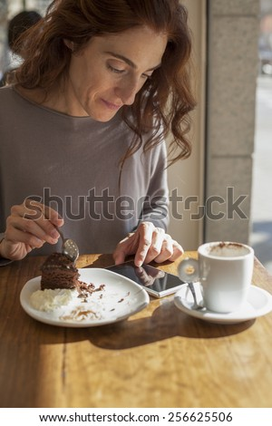 woman taking chocolate cake piece with spoon next to white small cup cappuccino coffee and touching mobile phone blank screen on light brown wooden table - stock photo