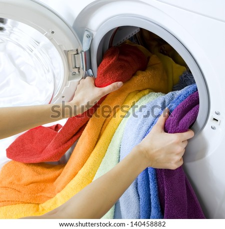 woman taking color  clothes from washing machine - stock photo