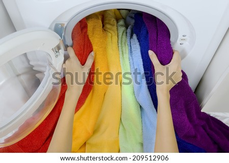 woman taking color laundry from washing machine - stock photo