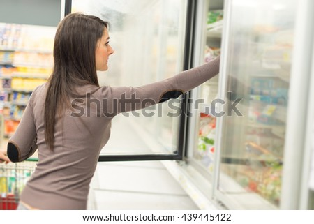Woman taking deep frozen food from a freezer in a supermarket - stock photo