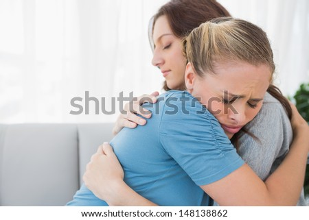 Woman taking her friend in her arms and sitting on the sofa - stock photo