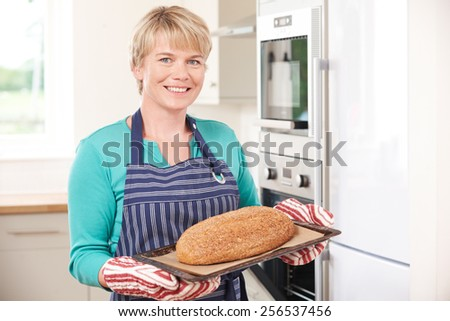 Woman Taking Home Baked Loaf Out Of Oven - stock photo
