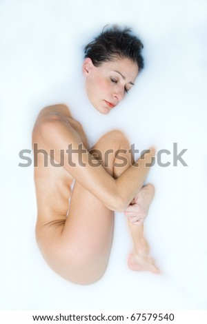 Woman taking milk bath. - stock photo