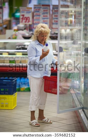 Woman taking milk from the fridge in supermarket - stock photo