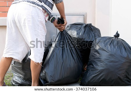 Woman Taking Out Garbage In black bags - stock photo