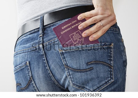 Woman taking passport out of the back pocket - stock photo