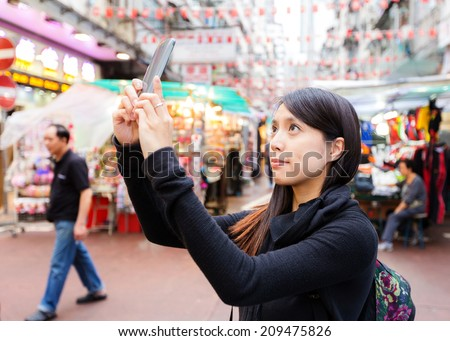 Woman taking photo in Hong Kong downtown street - stock photo