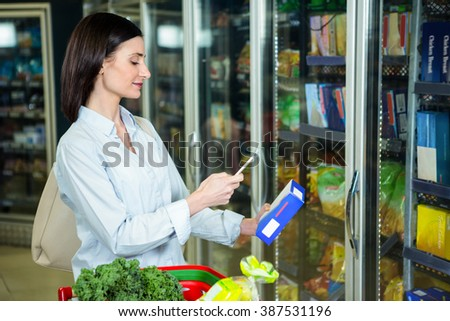 Woman taking photo of a box in supermarket - stock photo