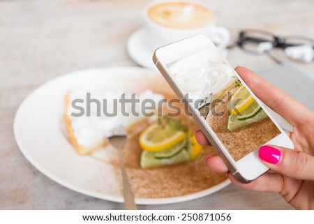 Woman taking photo of her cake in cafe with mobile phone - stock photo
