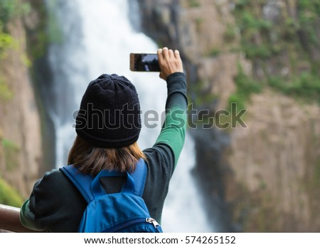 Woman taking photo waterfall in forest by cellphone