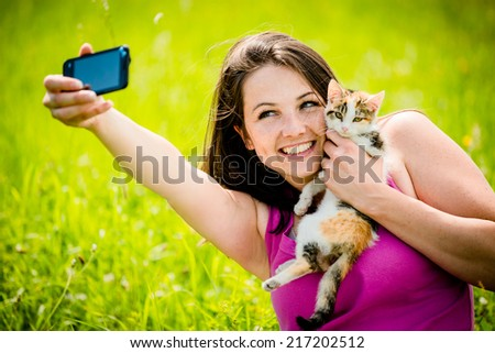 Woman taking photo with mobile phone camera of herself and her cat - outdoor in nature - stock photo