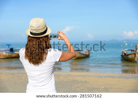 Woman taking photos with smartphone at Railay Beach, Krabi, Thailand. - stock photo