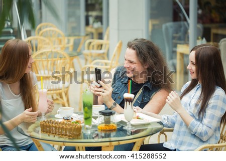 Woman taking picture of her friends in the coffee shop