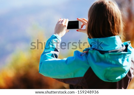 Woman taking picture with smartphone during autumn in mountains - stock photo