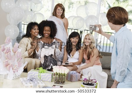 Woman Taking Pictures of friends sitting on sofa at Party - stock photo