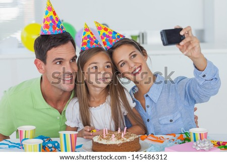 Woman taking pictures of her family during her daughter birthday party - stock photo