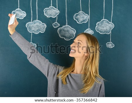 Woman taking selfie with cloud computing concept - stock photo
