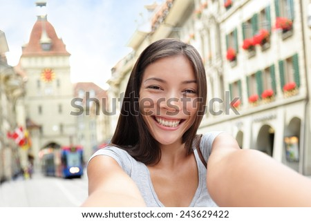 Woman taking selfie with smart phone in Bern Switzerland walking on Kramgasse, Berne main street in the old city. Young female visiting tourist attractions and landmarks. - stock photo