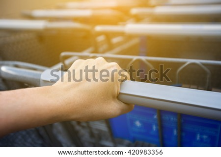Woman taking shopping cart near supermarket. Closeup on female hand holding shop trolley