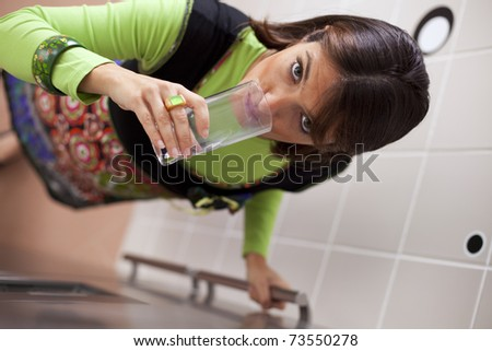 woman taking some water from her refrigerator (selective focus with shallow DOF) - stock photo