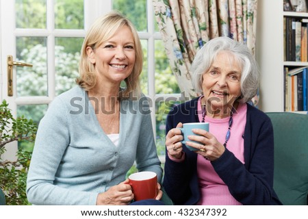 Woman Taking Time To Visit Senior Female Neighbor And Talk - stock photo