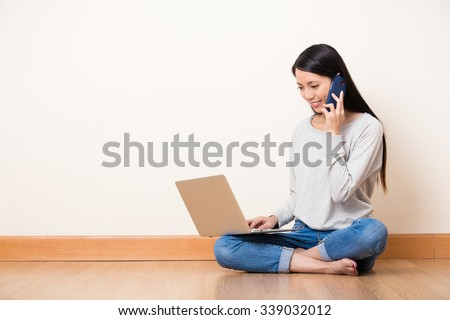 Woman talk to someone by mobile phone with watch on the laptop computer - stock photo