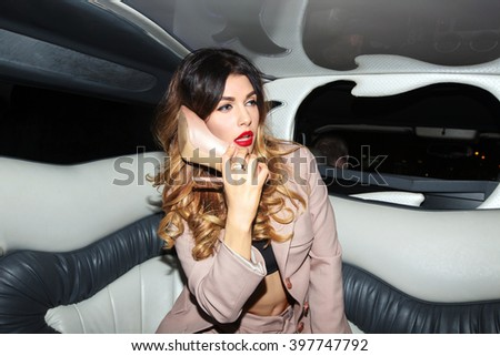 Woman talking on a shoe as on the phone in the car with the driver in a pink business suit with bright makeup and shoes with heels sitting in a car, limousine - stock photo