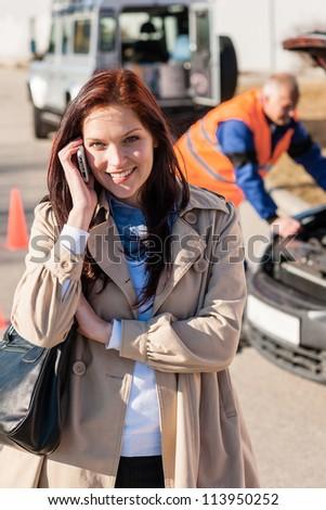 Woman talking on cellphone after car breakdown trouble problem mechanic - stock photo