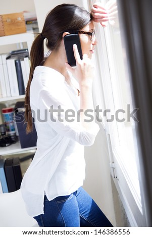 woman talking on mobile phone at work