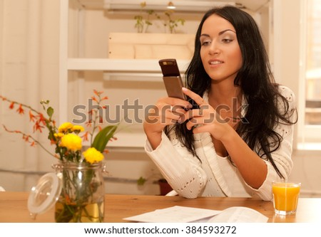 woman talking on phone in her living room - stock photo