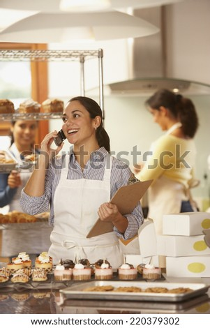 Woman talking on phone while working in bakery - stock photo