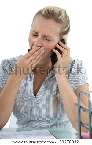woman talking on the phone and yawning - stock photo