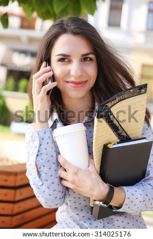 Woman talking on the phone. Business woman on the street. Business casual style. The girl with a glass of coffee. Joyful woman. Office worker. Young woman with diary. - stock photo