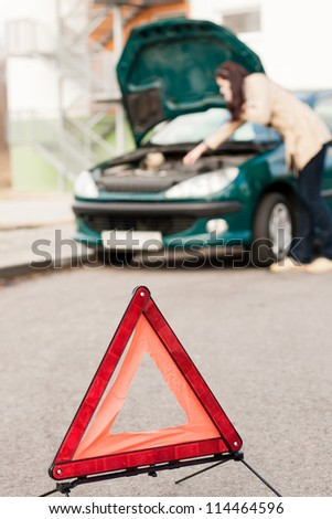 Woman talking on the phone car breakdown hood checking trouble - stock photo