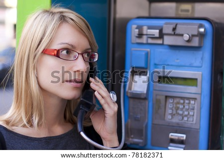 Woman talking on the phone in a retro phone boot - stock photo