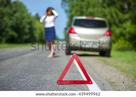 Woman talking on the phone near broken car, red triangle warning sign closeup