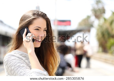 Woman talking on the phone taking a conversation while is waiting in a train station - stock photo
