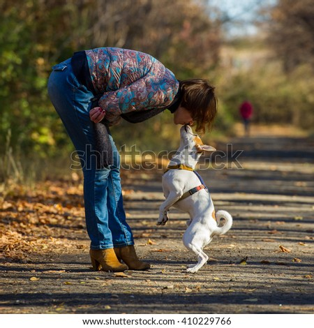 woman talking to a pet for a walk in the autumn park - stock photo