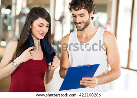 Woman talking to her personal trainer in a gym - stock photo