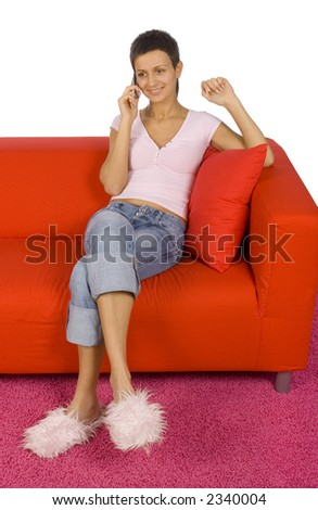 woman talking to the mobile; sitting on the red sofa - stock photo