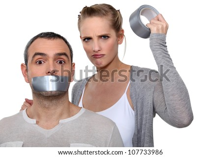 Woman taping boyfriends mouth closed - stock photo